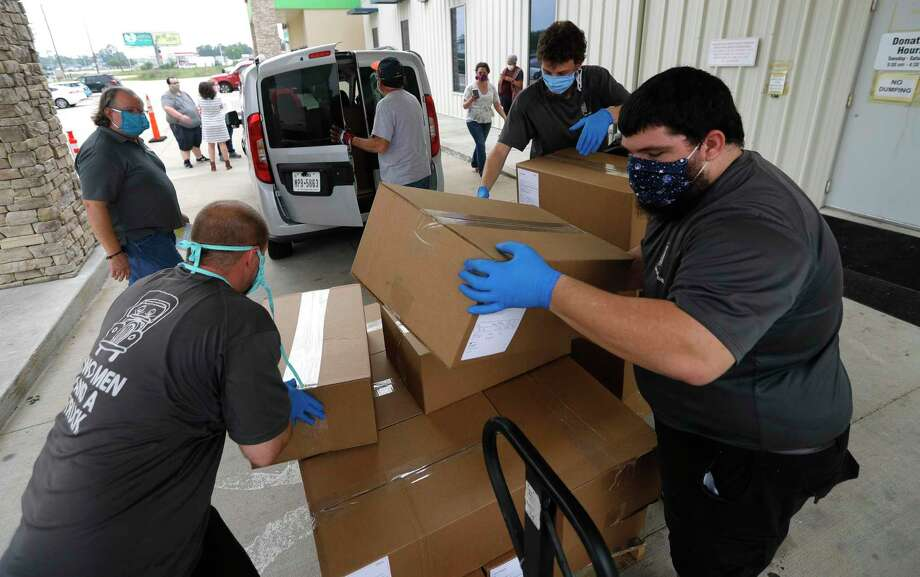 Joshua Lowe, left, Michael Briner, and Kendrall Fessas help load 3,000 facemask for health professionals at the Habitat for Humanity ReStore, Wednesday, April 22, 2020, in Conroe. Several boxes of facemasks were earmarked for Montgomery County hospitals, while others were sent to Harris County Hospital District, as well as Houston Methodist Hospital, CHI St. Luke's Hospital and Memorial Hermann Hospital in the Texas Medical Center. Photo: Jason Fochtman, Houston Chronicle / Staff Photographer / 2020 © Houston Chronicle