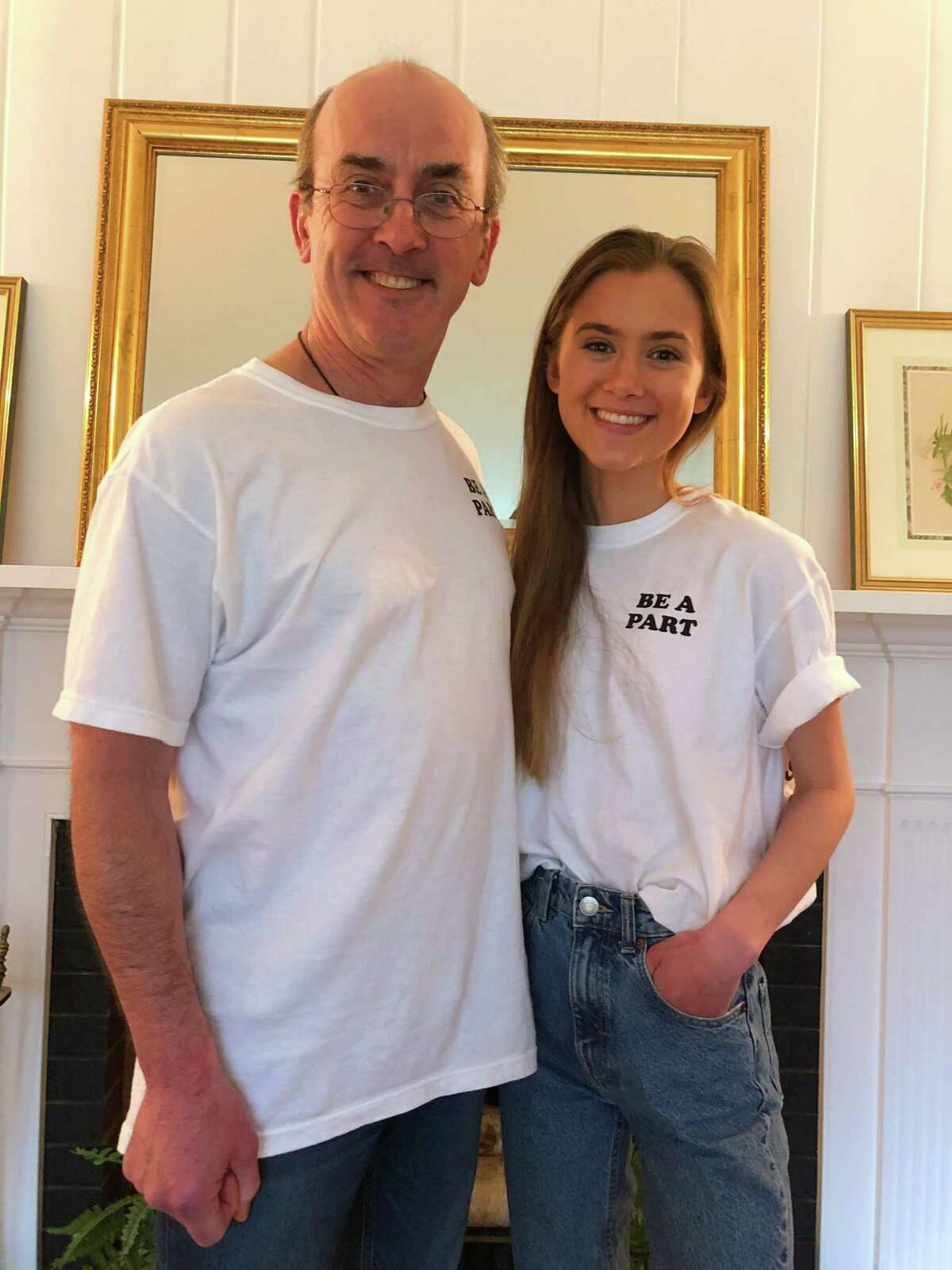 Margaux Kelley and her dad Brian wear the t-shirt she created to support local food banks.