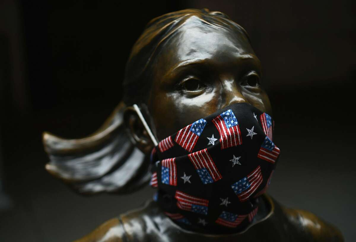"""The """"Fearless Girl"""" statue wears a face mask with American Flags outside the New York Stock Exchange, Wall street on April 23, 2020 in New York City. - More than one in five New Yorkers may have already had the new coronavirus, a testing sample showed April 23, 2020, suggesting infections are much higher than confirmed cases suggest. Widespread testing -- including for antibodies -- is viewed as key to American states being able to lift stay-at-home orders and reopen their shuttered economies. (Photo by Angela Weiss / AFP) (Photo by ANGELA WEISS/AFP via Getty Images)"""