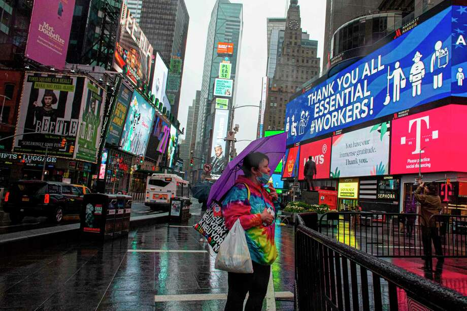 A woman covers herself from the rain as she visits Times Square amid the coronavirus pandemic in New York City. Photo: Getty Images / AFP