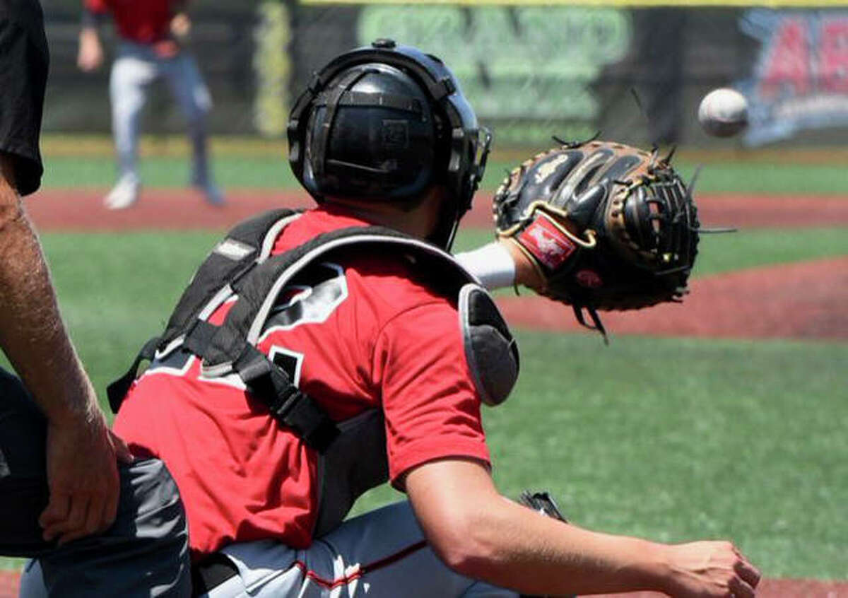 Edwardsville senior Nic Hemken receives a pitch at catcher during a game with his club team.