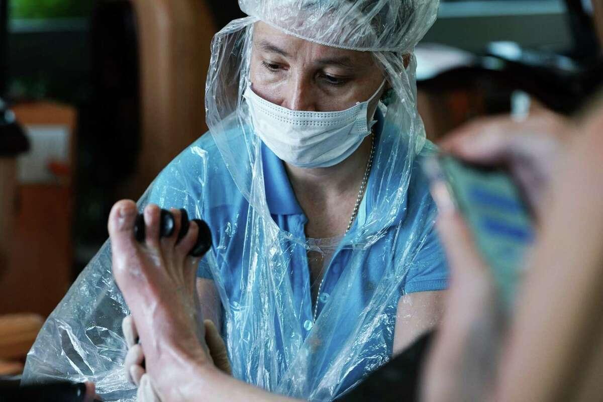 A worker gives a customer a pedicure at a nail salon in Atlanta on April 24, 2020.