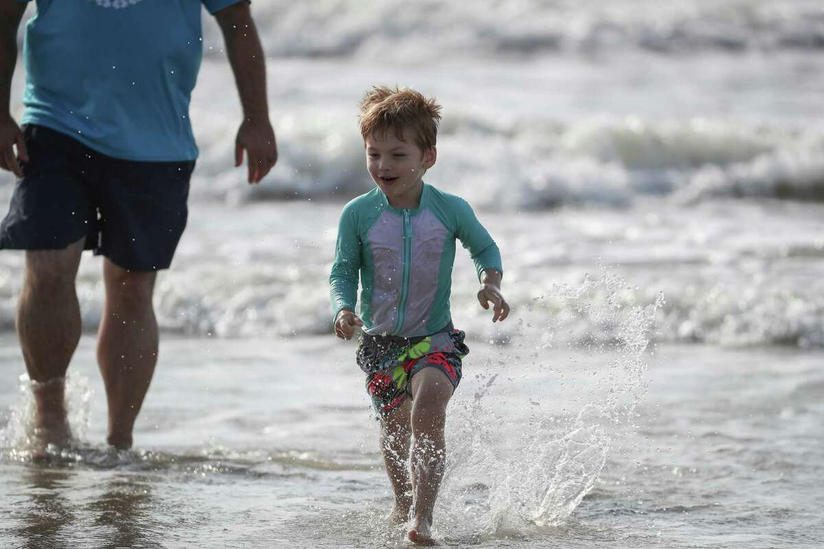 Miles Tomaino, 3, runs on the beach as his father, Jesse keeps an eye on him after the city of Galveston partially reopen public beaches after closing them for nearly a month due to the novel coronavirus outbreak Monday, April 27, 2020, in Galveston. The Tomaino family are from Oregon decided to shelter in place in Galveston instead of driving across the United States to return home.