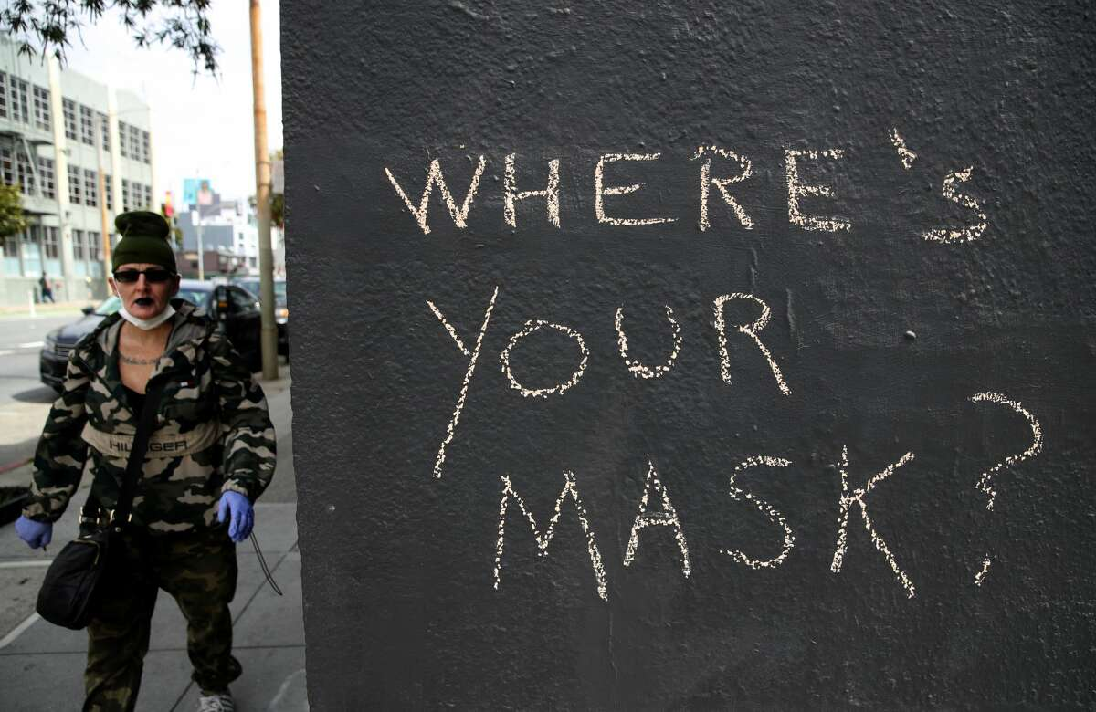 A pedestrian walks by graffiti encouraging the wearing of masks on April 20, 2020 in San Francisco, California. Counties in the San Francisco Bay Area have announced that people must wear masks when in public or at the workplace in an effort to slow the spread of coronavirus COVID-19. (Photo by Justin Sullivan/Getty Images)