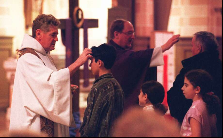 Ash Wednesday was celebrated by Catholics in the area with services and distribution of the ashes in 2001. At St. Cecilia's Church on Newfield Avenue in Stamford the Rev. Roger Watts, left, the pastor, and the Rev. William Carey blessed the faithful. Photo: / ST
