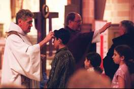 Ash Wednesday was celebrated by Catholics in the area with services and distribution of the ashes in 2001. At St. Cecilia's Church on Newfield Avenue in Stamford the Rev. Roger Watts, left, the pastor, and the Rev. William Carey blessed the faithful.