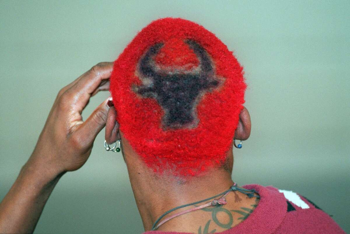 Dennis Rodman, sporting red hair with a Bulls insignia in the back, speaks during a news conference during media day at the Chicago Bulls training center in Deerfield, Ill, Thursday Oct. 5, 1995. Rodman is now a teammate of one-time adversaries Michael Jordan and Scottie Pippen as camp opens Thursday for the team. (AP Photo/Beth A. Keiser)