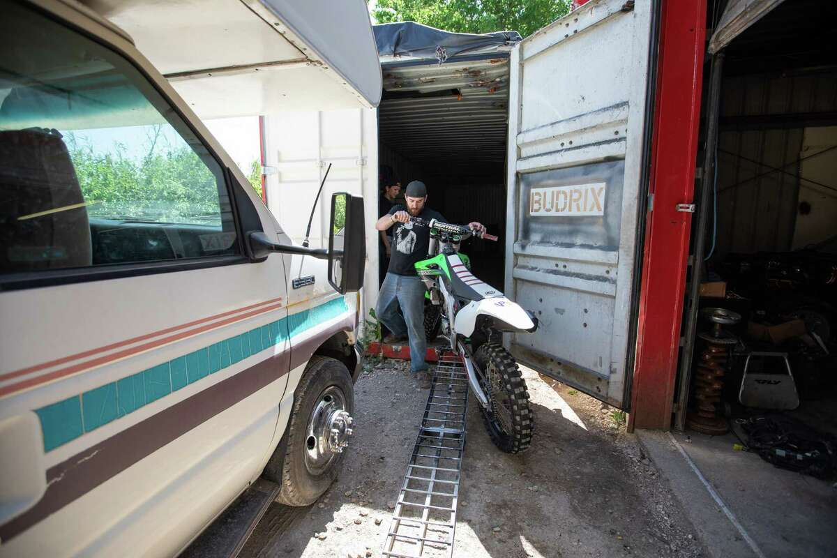 Bud Allen removes client motorcycles that must be sold or reclaimed before closing his business on Friday, April 24, 2020 in Buda, Texas.