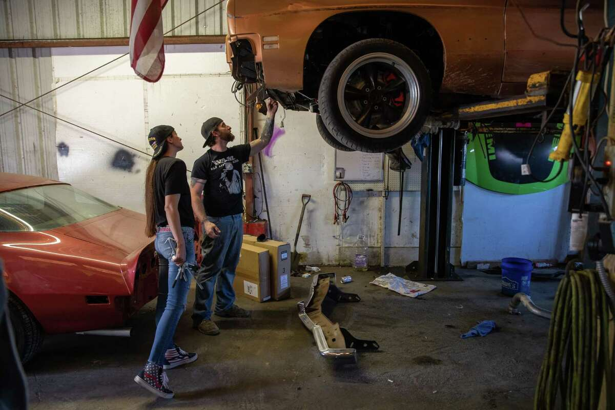 Bud and Amanda Allen check the progress on a client vehicle at their repair shop on Friday, April 24, 2020 in Buda, Texas. The Allens must complete repairs on existing vehicles or ask clients to retrieve incomplete repairs before they move to Tyler.