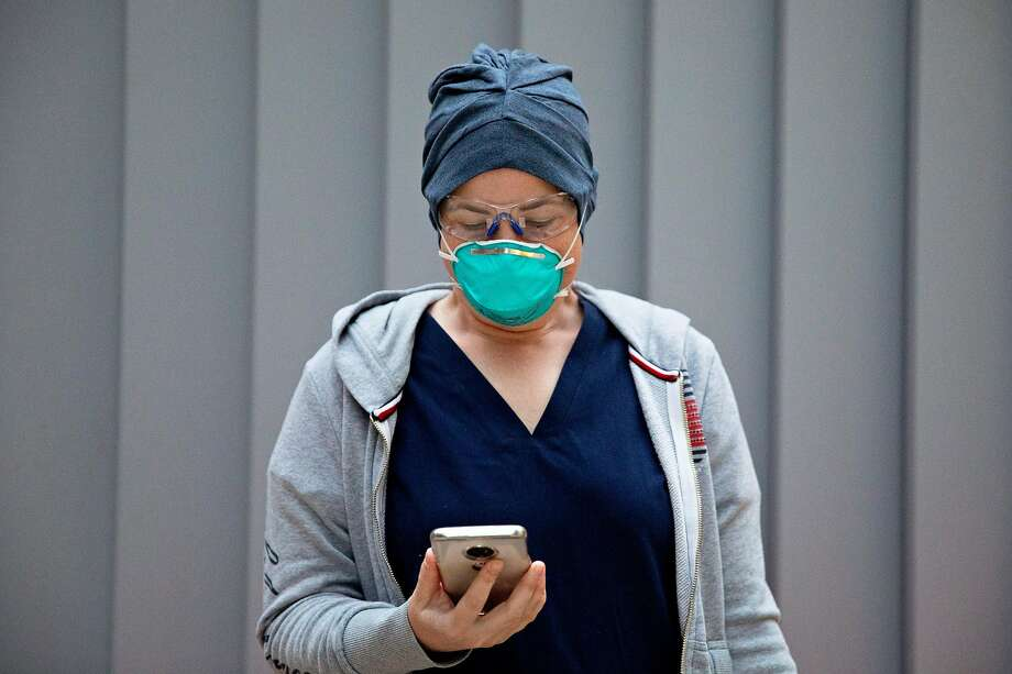 Emergency Department nurse Christa Duran checks her pre-screening app on her phone while wearing full personal protective equipment before starting her morning shift at San Francisco General Hospital in San Francisco, Calif. Saturday, April 11, 2020. Photo: Jessica Christian / The Chronicle