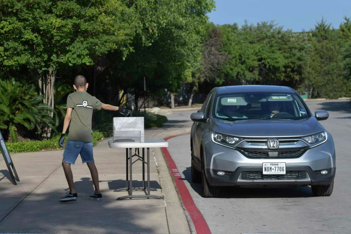 A workerat the Shops at La Cantera delivers merchandise curbside on Friday, April 24, 2020.