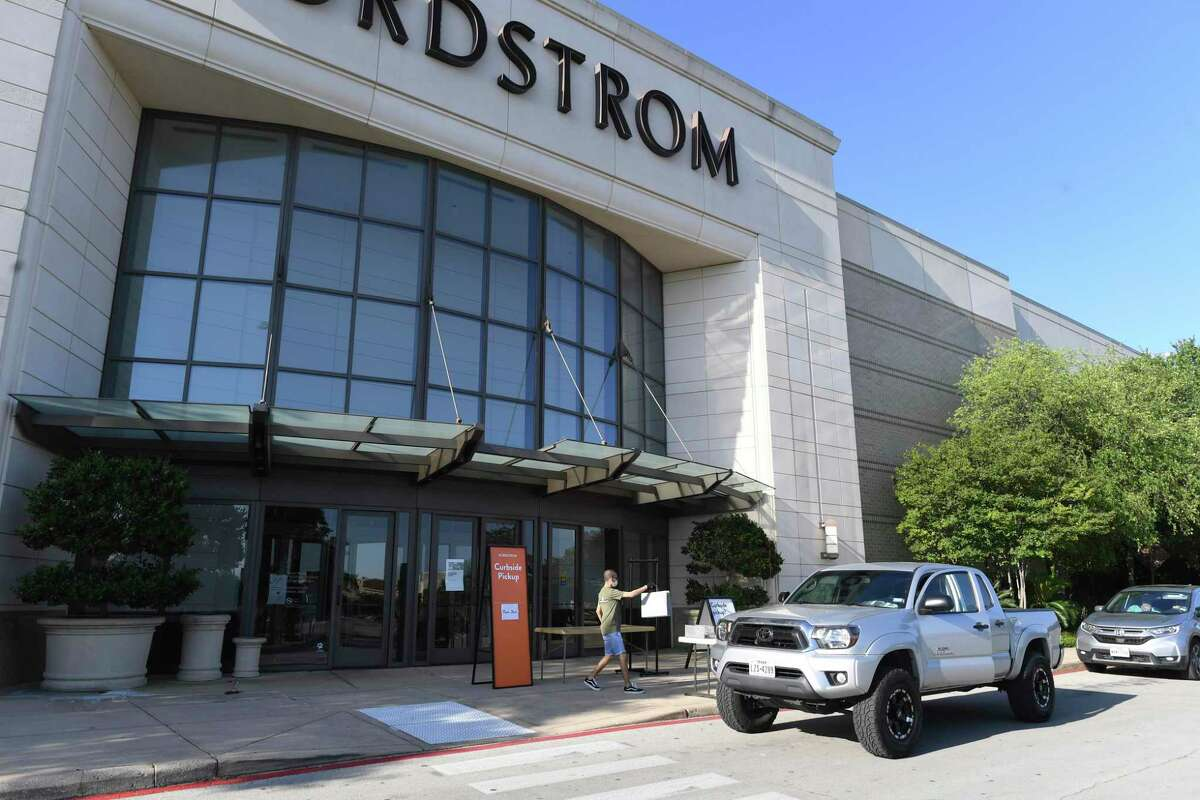 """A worker at Nordstrom at the Shops at La Cantera delivers merchandise curbside Friday. """"Non-essential"""" Texas businesses were allowed to open, but only with customers able to drive up to pick up items."""