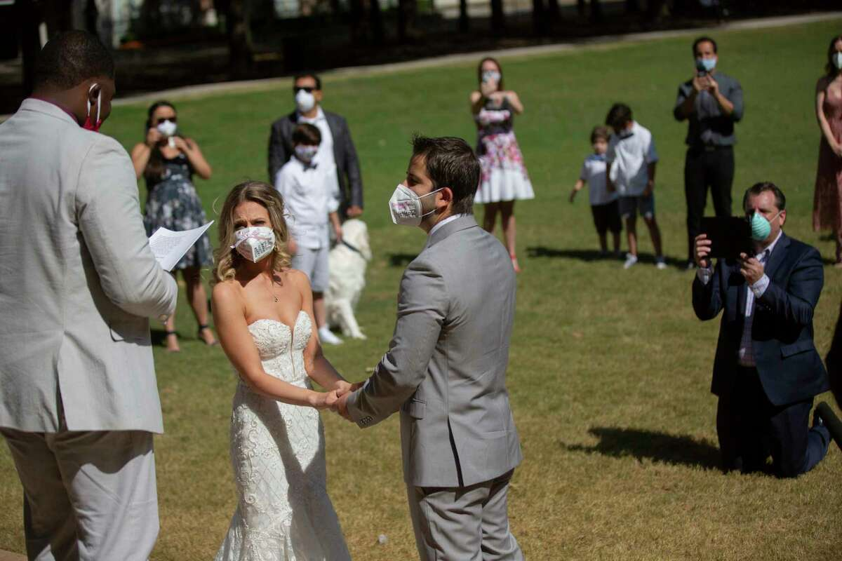 Gabrielle Schmees, 29, and Diego Grassano, 31, get married wearing protective masks at the Gerald D. Hines Waterwall Park on Monday, April 27, 2020, in Houston. Their friend Torrance Wilson officiates the wedding.Because of COVID-19, the couple decided to postpone their official wedding and have a small one at the Waterwall Park until December when they can have the official one with all of their family and friends.