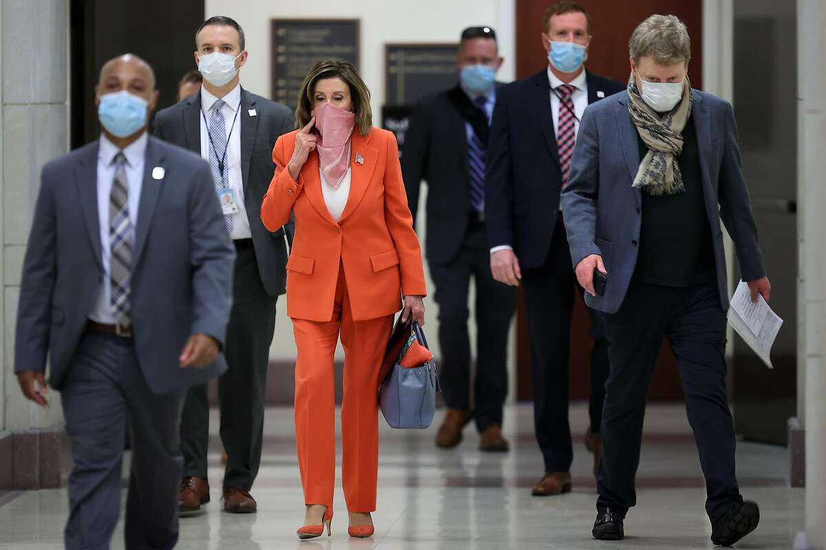 WASHINGTON, DC - APRIL 24: Wearing a scarf over her mouth and nose, Speaker of the House Nancy Pelosi (D-CA) is surrounded by security and staff as she arrives for her weekly news conference during the novel coronavirus pandemic at the U.S. Capitol April 24, 2020 in Washington, DC. President Donald Trump is expected to sign a bipartisan $484 billion coronavirus relief package to restart a depleted small business loan program and to provide funds for hospitals and COVID-19 testing. (Photo by Chip Somodevilla/Getty Images) *** BESTPIX ***