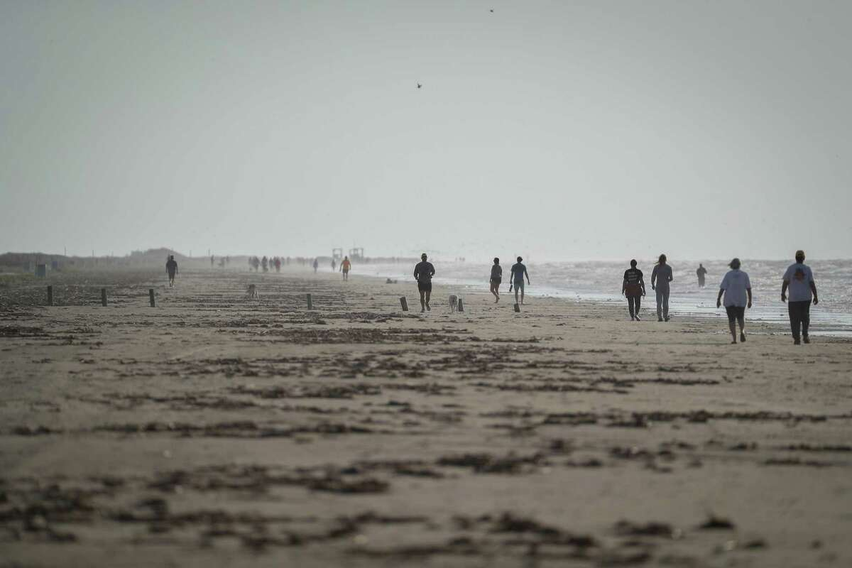 People walk and run on the beach after the city of Galveston partially reopen public beaches after closing them for nearly a month due to the novel coronavirus outbreak Monday, April 27, 2020, in Galveston.