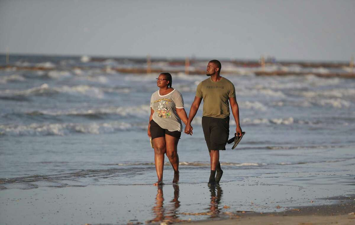 Tulsa, OK residents Sierra Higbee and Philanteus Jarrett walk the beach after the city of Galveston partially reopen public beaches after closing them for nearly a month due to the novel coronavirus outbreak Monday, April 27, 2020, in Galveston. Higbee said that she just need a break from the quarantine and when she heard that Galveston's beaches were opening up, she and Jarrett booked a flight to Texas.
