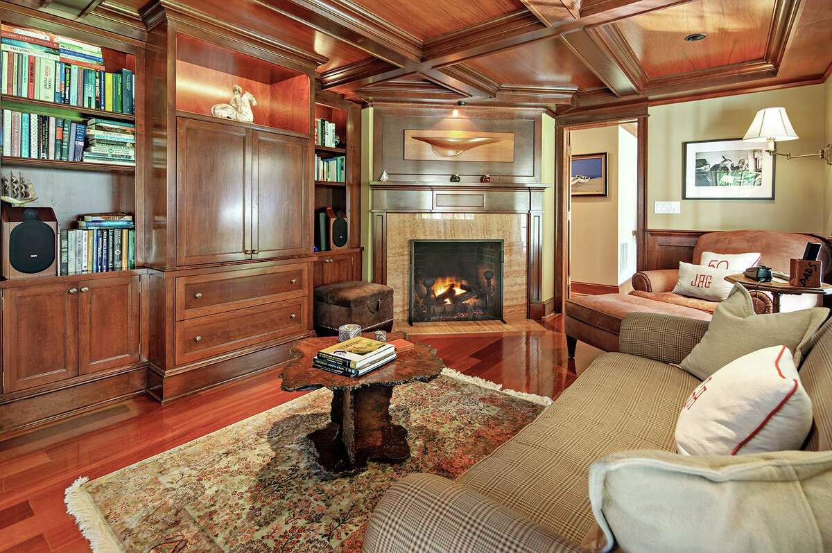 The den features a fireplace, coffered ceiling, and built-in bookshelves and cabinetry.
