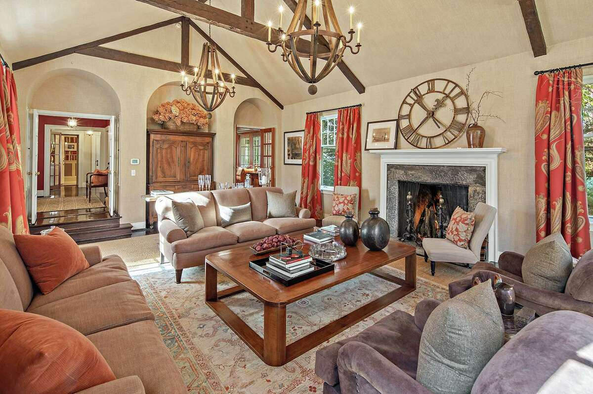 The living room features a cathedral ceiling, fireplace and exposed beams.