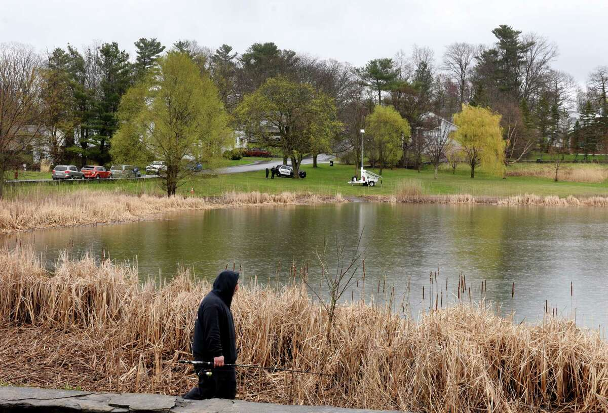 An angler walks the perimeter of Steinmetz Park pond where there were reports of a possible alligator sighting on Monday, April 27, 2020, in Schenectady, N.Y. New York State Department of Environmental Protection officers searched the pond and found a large snapping turtle, but no signs of an alligator. (Will Waldron/Times Union)