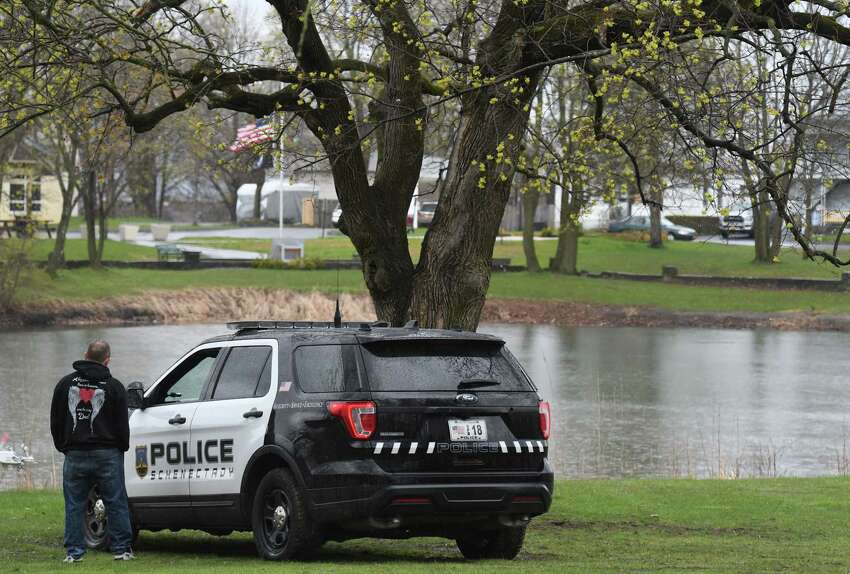 A Schenectady Police officer is posted at Steinmetz Park pond where there were reports of a possible alligator sighting on Monday, April 27, 2020, in Schenectady, N.Y. New York State Department of Environmental Protection officers searched the pond and found a large snapping turtle, but no signs of an alligator. (Will Waldron/Times Union)
