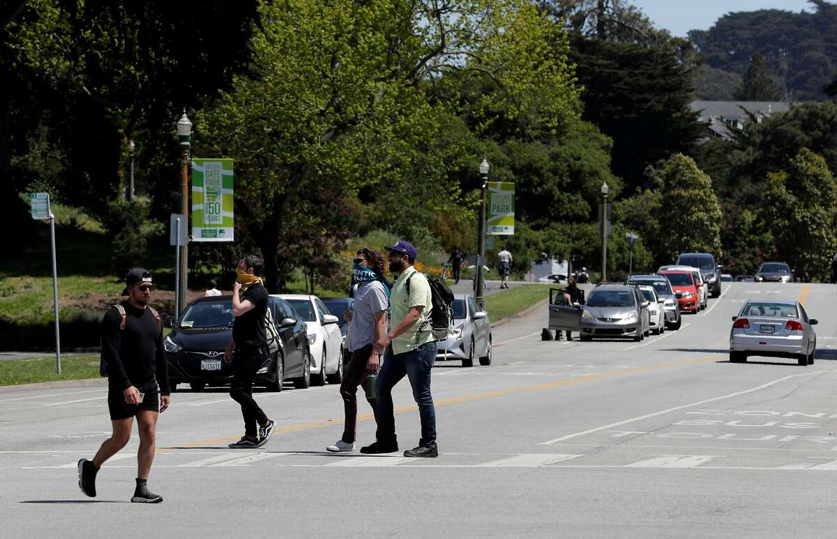 Pedestrians cross John F. Kennedy Drive in Golden Gate Park in San Francisco, Calif., on Monday, April 27, 2020. City health officials extended the stay at home order until the end of May, and will be shutting down the street to vehicle traffic.