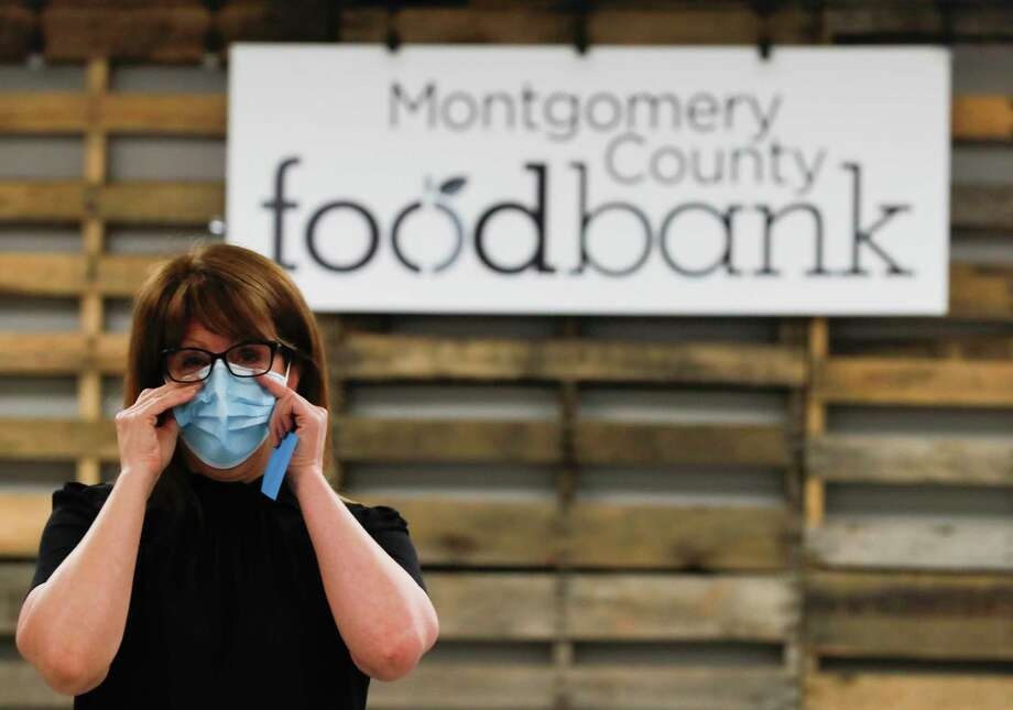 Allison Hulett, president and CEO of the Montgomery County Food Bank, adjusts her facemask as she speaks to members of the National Guard, Tuesday, April 21, 2020, in Conroe. Governor Greg Abbott dispatched more than 2,500 guardsmen to serve in varying capacities around the state to help combat COVID-19. The food bank was granted $80,000 this month from the Greater Houston COVID-19 Recovery Fund to purchase food staples and feed 100,000 families. Photo: Jason Fochtman, Houston Chronicle / Staff Photographer / 2020 © Houston Chronicle
