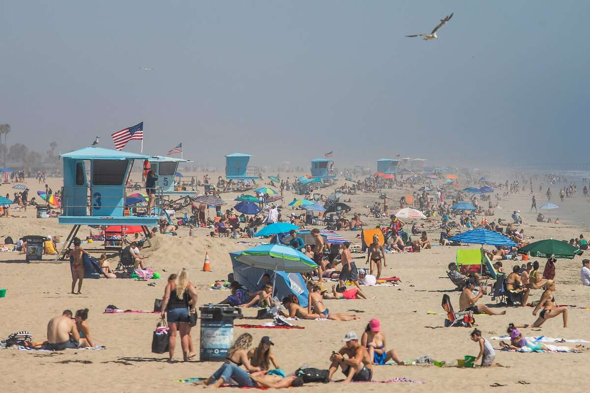 People enjoy the beach amid the novel coronavirus pandemic in Huntington Beach, California on April 25, 2020. - Orange County is the only county in the area where beaches remain open, lifeguards in Huntington Beach expect tens of thousands of people to flock the beach this weekend due to the heat wave. Lifeguards and law enforcement are patrolling the beach to make sure people are keeping their distance. (Photo by Apu GOMES / AFP) (Photo by APU GOMES/AFP via Getty Images)
