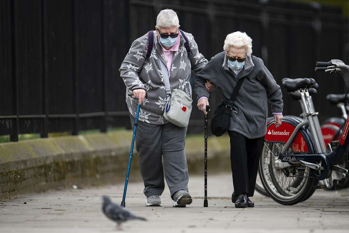 Elderly members of the public wearing face masks walk down a street in Central London on April 01, 2020 in London, England.