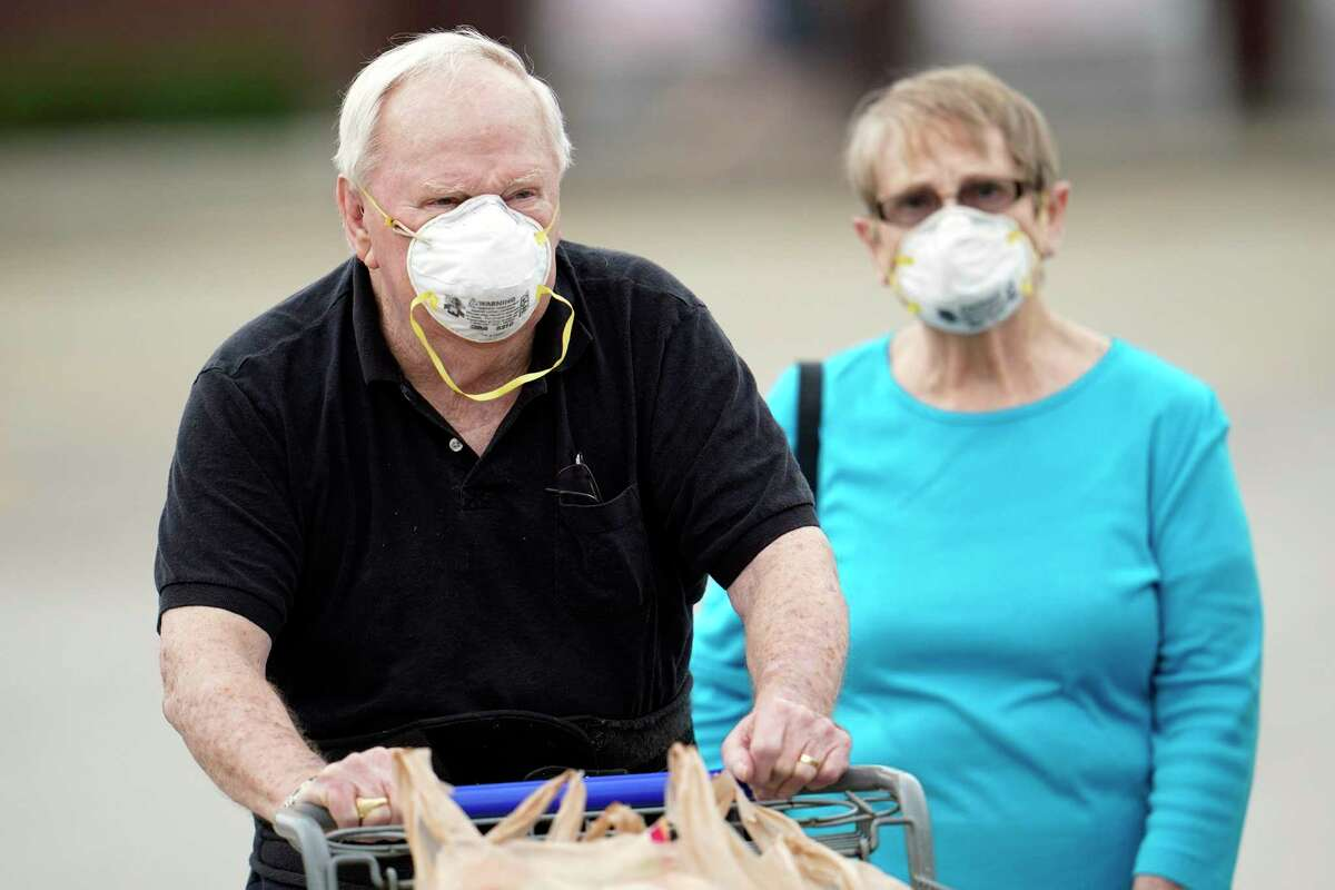 Shoppers wear face masks to protect against COVID-19 as they leave a grocery store last week in Spring. One reader says wearing a mask in public is doing your part to protect everyone else.