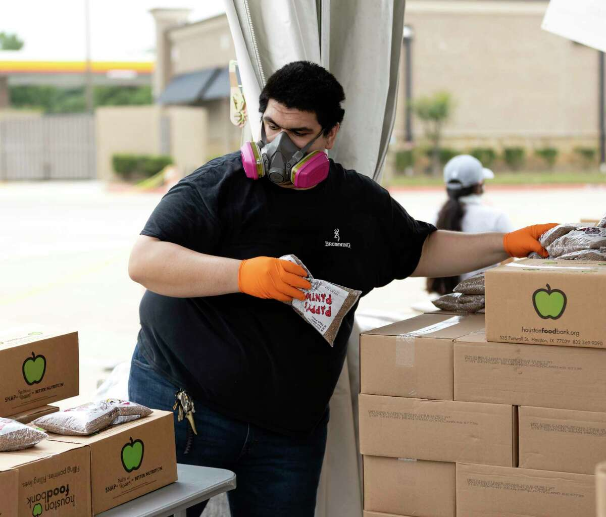 Rafael Soltero adds bagged beans to food boxes at the Houston Premium Outlets in Cypress, Wednesday, April 22, 2020. The Houston Food Bank, in partnership with Cy-Hope hosted a mega weekly food distribution event that assisted over 6,000 families.