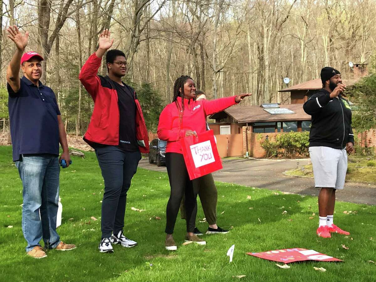 Lucas Niang, far right, and family wave to passers by during a parade in front of the family home on Saturday, April 25, 2020 in New Canaan, Conn. Lucas Niang, a New Canaan alum, was drafted by the Kansas City Chiefs the day before.