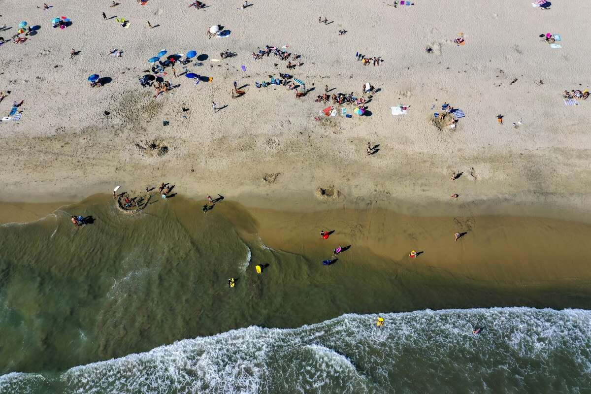 NEWPORT BEACH, CA -- SATURDAY, APRIL 25, 2020: An aerial view of thousands of beach-goers enjoying a warm, sunny day at the beach amid state-mandated stay-at-home and social distancing mandate to stave off the coronavirus pandemic in Newport Beach, CA, on April 25, 2020. (Allen J. Schaben / Los Angeles Times via Getty Images)