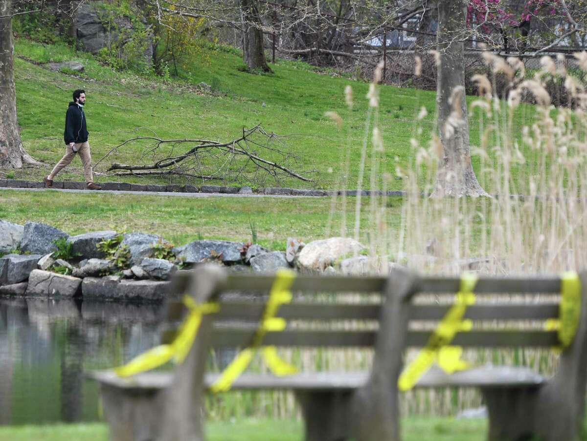 Greenwich's Santiago MacLean walks on a path as park benches are taped off at Bruce Park in Greenwich, Conn. Monday, April 27, 2020. Certain parks have reopened with access restricted to just the sidewalks and walking paths with social distancing precautions still in effect.