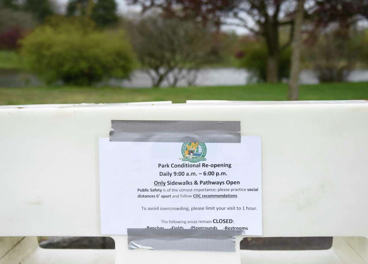 A sign is posted at Bruce Park in Greenwich, Conn. Monday, April 27, 2020. Certain parks have reopened with access restricted to just the sidewalks and walking paths with social distancing precautions still in effect.