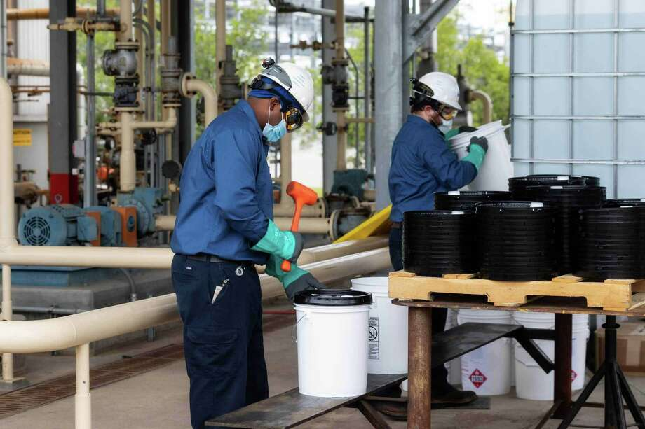 Exxon Mobil manufacturing plant personnel package sanitizers outdoors. Photo: Associated Press