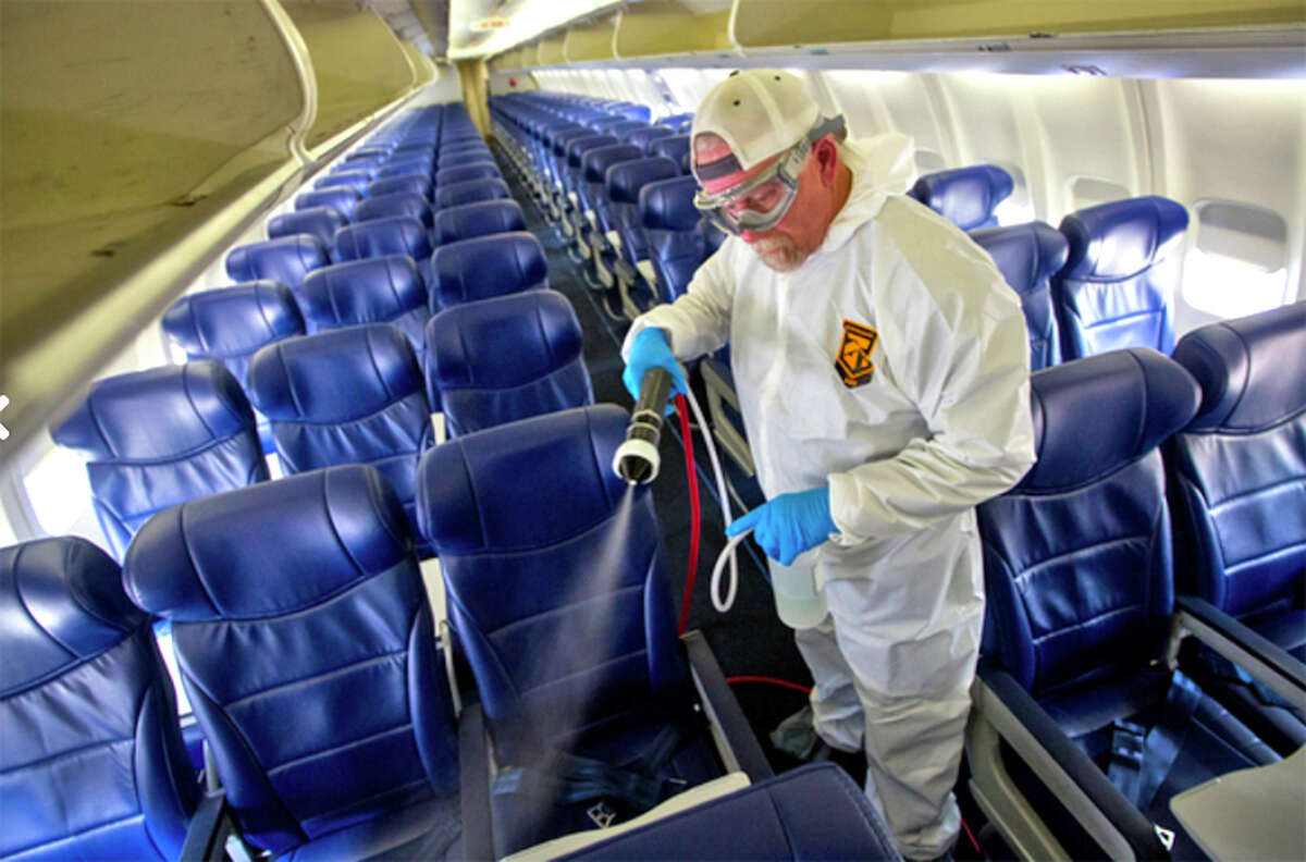 A Southwest employee sprays down passenger seats.