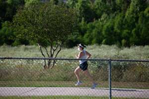 A woman runs along the White Oak Bayou trail on April 27, 2020, in Houston. Harris County Judge Lina Hidalgo's order to wear face masks in public went into effect Monday.