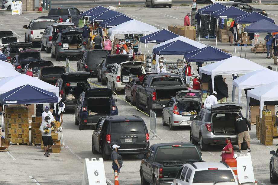 Vehicles drive by different stations to pick up food during a San Antonio Food Bank mega donation at NISD Hardin Athletic Complex, Tuesday, April 21, 2020. The food bank was expecting to serve 2,600 households. Photo: Jerry Lara, San Antonio Express-News
