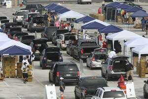 Vehicles drive by different stations to pick up food during a San Antonio Food Bank mega donation at NISD Hardin Athletic Complex, Tuesday, April 21, 2020. The food bank was expecting to serve 2,600 households.