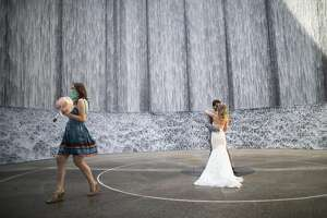 Gabrielle Schmees, 29, and Diego Grassano, 31, have their first dance as husband and wife on the day of their wedding at the Gerald D. Hines Waterwall Park on Monday, April 27, 2020, in Houston. Because of COVID-19, the couple decided to postpone their official wedding and have a small one at the Waterwall Park until December when they can have the official one with all of their family and friends.
