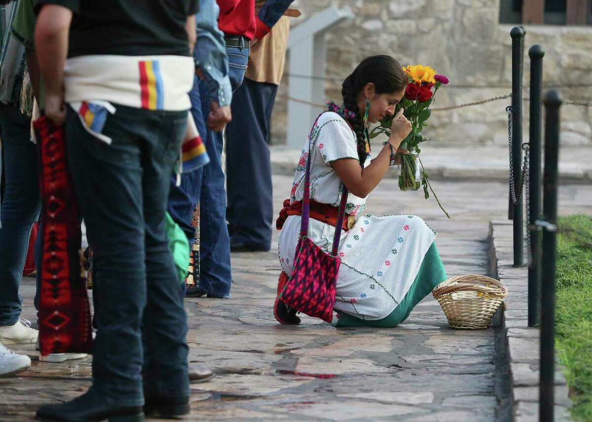 Vanessa Quezada kneels to pray and honor indigenous descendants buried at the Alamo as local Native Americans gather during their 25th Annual Sunrise Ceremony at the Alamo on Saturday, Sept. 7, 2019. Ramon Juan Vasquez, executive director of American Indians in Texas at the Spanish Colonial Missions, along with over 60 people who claim ancestry with the Native Indians who are buried on the grounds of the Alamo, formed a circle in front of the church to pray and honor their descendants. In the past, the group was allowed to have the service inside the chapel but were told days before the event that the service would not be permitted inside the Alamo. With a noticeable presence of Alamo security officers and chain blocking the walking to the front doors, the group formed a circle on Alamo Plaza to air their grievances and to remember their descendants. Vasquez and the group was joined by State Senator Jose Mendendez, State Rep. Leo Pacheco and Poet Laureate Carmen Tafolla who all expressed dismay that the indigenous group would not be allowed to pray and honor their loved ones inside the Alamo. Despite the prohibition, members of the Tap Pilam Coahuiltecan Nation and other indigenous people paid their respects on the ground by the front of the Alamo. A shell filled with sage slowly burned and filled the early morning sky with wafts of smoke - which traditionally serves to bless and purify - as the service ended just as the sun rose over the Alamo. (Kin Man Hui/San Antonio Express-News)