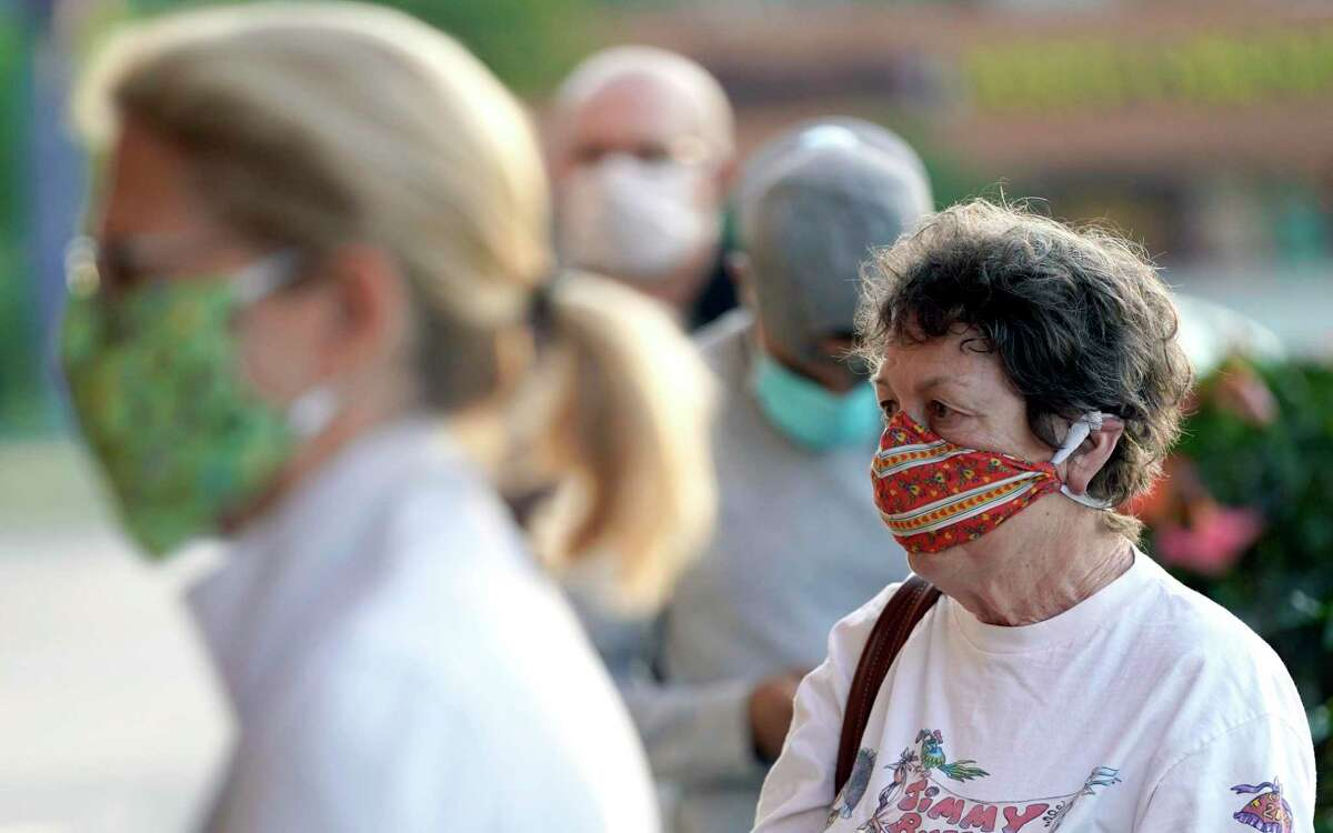 Shoppers wear face masks, to help prevent the spread of COVID-19, as they wait to enter a store Monday, April 27, 2020, in Houston. (AP Photo/David J. Phillip)