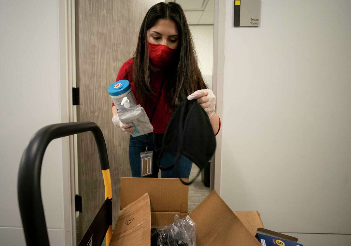 Alejandra Ramos, 23, a junior paralegal clerk at AZA Law, disinfecting products and face masks to place at work stations Monday, April 27, 2020, in Houston. Many companies are preparing for their employees to return to work.