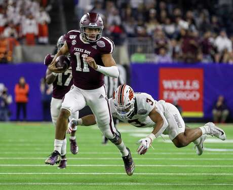 Oklahoma State Cowboys safety Tre Sterling (3) dives after Texas A&M Aggies quarterback Kellen Mond (11) as he rushes for a first down during the fourth quarter of the Texas Bowl at NRG Stadium on Friday, Dec. 27, 2019, in Houston.