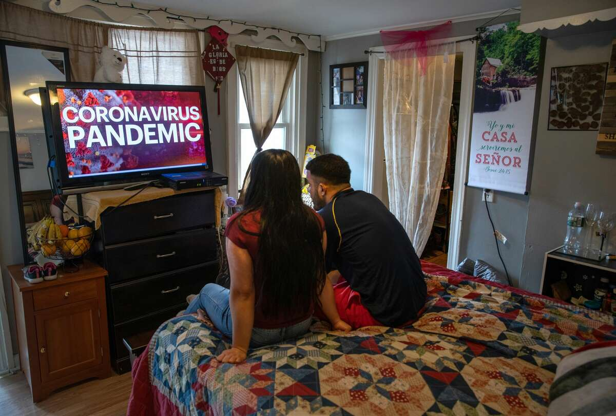 Undocumented immigrant Juana, 24, from El Salvador and her husband Saul, 23, from Honduras watch local news in their one-room apartment on March 25, 2020 in Norwalk, Connecticut. Juana lost her job as a house cleaner and Saul as a painter due to the coronavirus (COVID-19) pandemic. Undocumented immigrants cannot collect unemployment. Nor will they benefit from federal government bailout legislation.