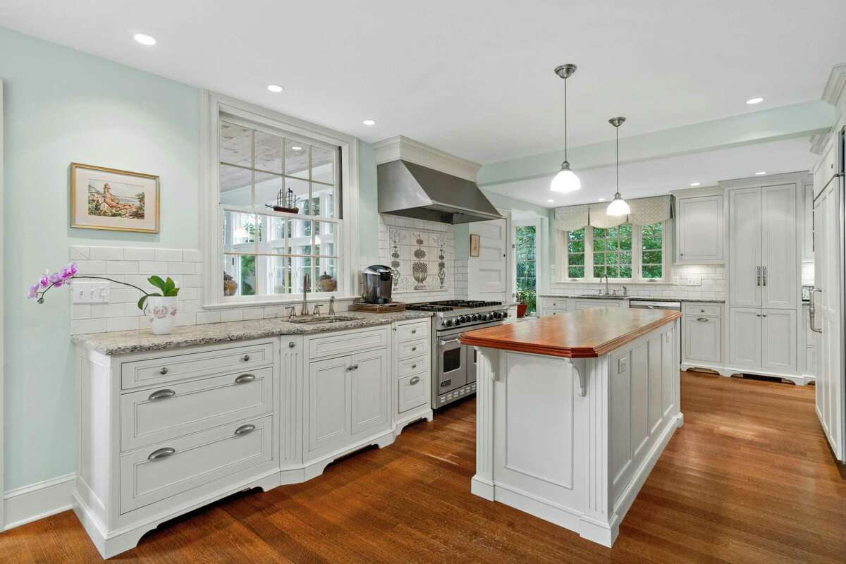 The updated kitchen features a center island, granite counters, a wood-burning brick fireplace with a beehive oven, and a decorative tile backsplash over the Viking six-burner gas range.