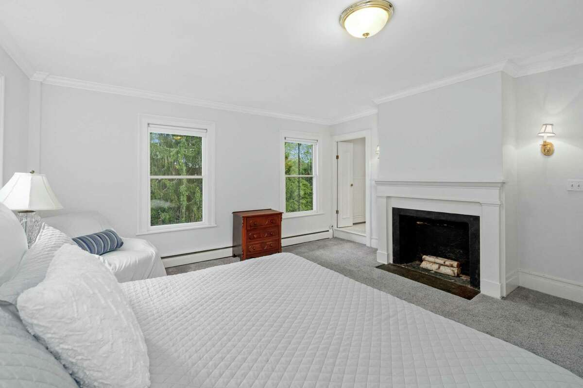 This house has four bedrooms, including the master suite, which has a fireplace and wall-to-wall carpeting.