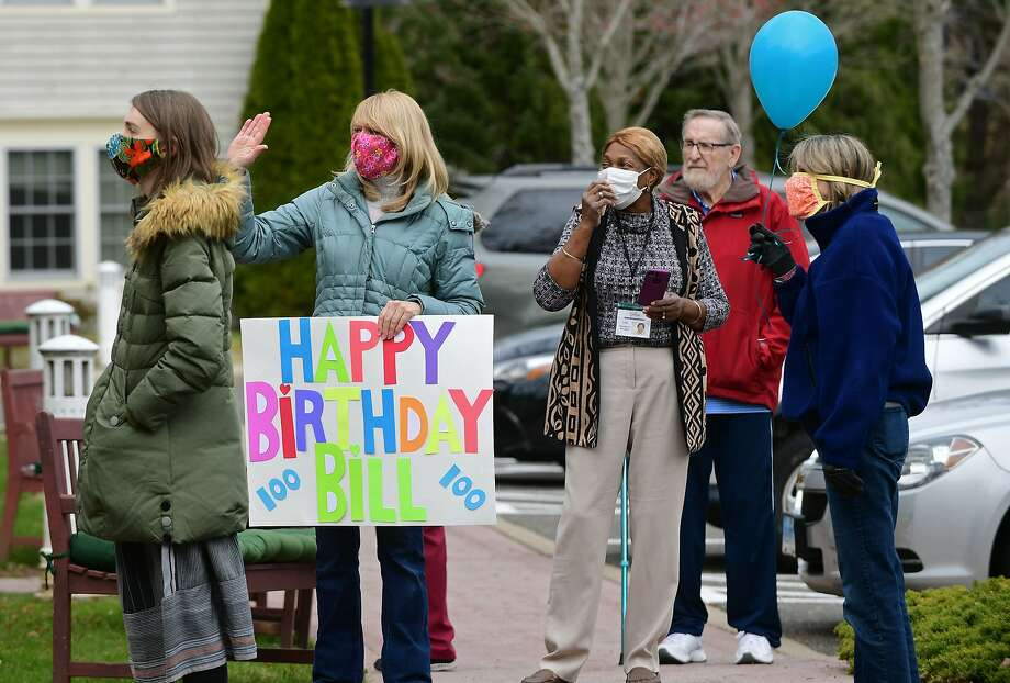Friends, family and the Wilton Police and Fire Departments hold a drive-by parade and hold signs of well-wishing for William Dunlap who celebrated his 100th birthday Thursday, April 23, 2020, at The Greens at Cannondale in Wilton, Conn. Photo: Erik Trautmann, Hearst Connecticut Media
