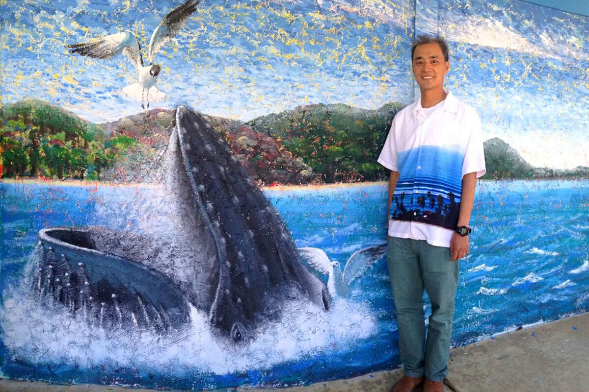 Above: Jeffrey Wong stands besides his Boys and Girls Club seascape featuring a humpback whale. Wong, 47, gave up his job as a chemical engineer at a high-tech firm four years ago. The stress of the job and the daily exposure to toxic gases became too overwhelming. While he had been painting in his free time, he wasn't immediately looking to make it a second career. He thought he'd give it a year and see what happened.