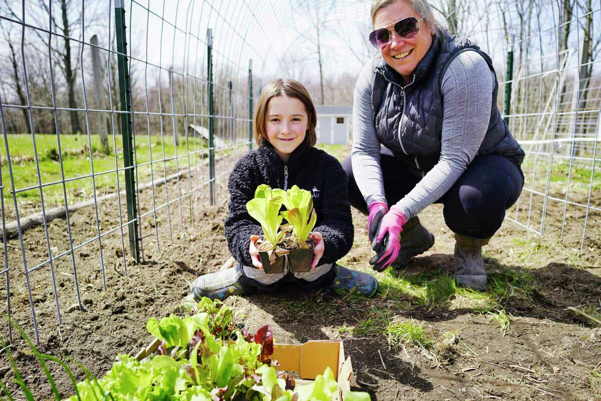 Stella Marcy, 10, left, and her mom, Jes Marcy, pose in their family garden on Thursday, April 23, 2020, in Poestenkill, N.Y. Stella is hold lettuce seedlings. (Paul Buckowski/Times Union)